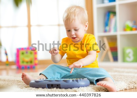 Happy kid boy playing piano toy in nursery room - stock photo