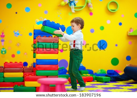 happy kid building blocks in kindergarten - stock photo