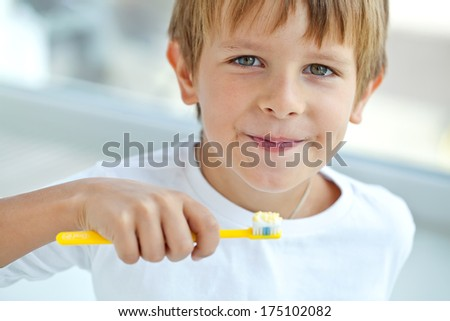 Happy kid cleans a teeth - stock photo