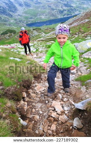 Happy kid climbs a winding mountain trail followed by his mother - stock photo