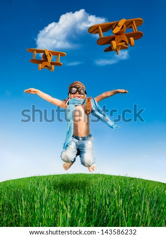 Happy kid dressed as a pilot jumping in green field against blue sky. Summer vacation concept - stock photo