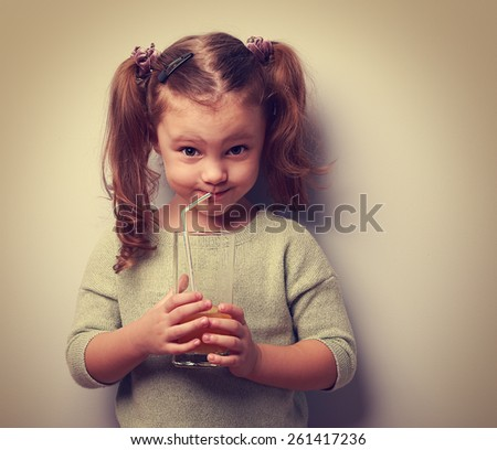 Happy kid drinking juice from glass and looking humor. Vintage portrait - stock photo