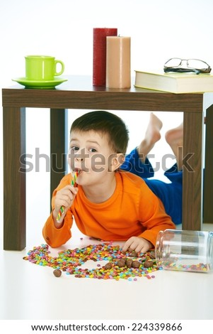 Happy kid eating lollipop under table sweets spilt. Home indoor, isolated on white. - stock photo