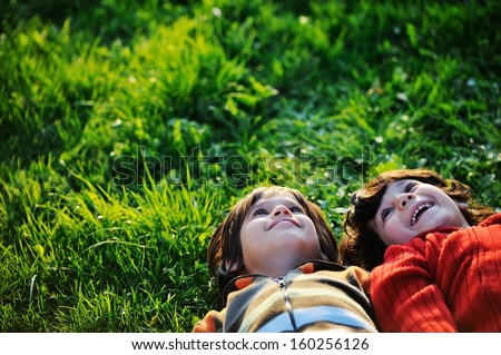 Happy kid enjoying sunny late summer and autumn day in nature on green grass