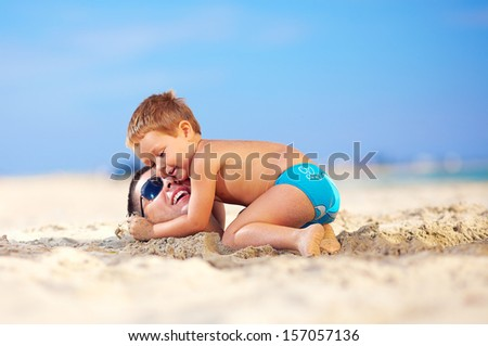 happy kid gently hugging father's head in sand on the beach - stock photo