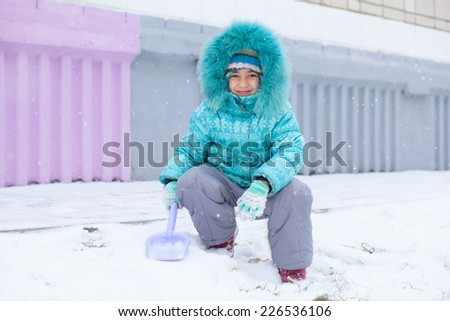 Happy kid girl child outdoors in winter playing with snow - stock photo