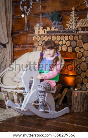 Happy kid girl having fun with wooden horse toy before christmas tree