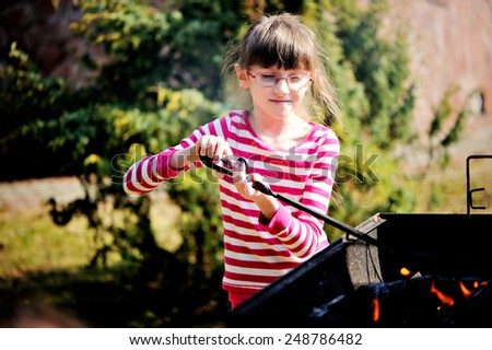 Happy kid girl helps with bbq on sunny spring day - stock photo