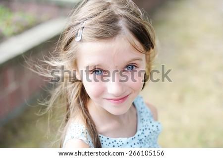 Happy kid girl  in beautiful dress, walking in the summer city - stock photo
