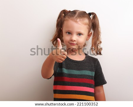 Happy kid girl showing thumb up sign and smiling on empty copy space background - stock photo