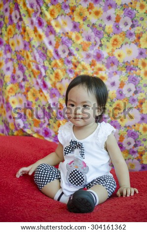 happy kid girl sitting on big red pillow - stock photo