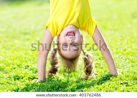 happy kid girl standing upside down on her head on grass in summer day - stock photo