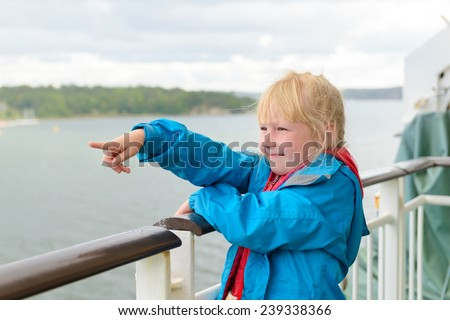 Happy kid girl traveling on ferry and pointing afar - stock photo