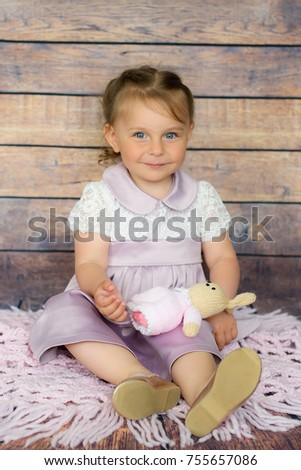 Happy kid girl with beautiful and big blue eyes laughing with on wooden background