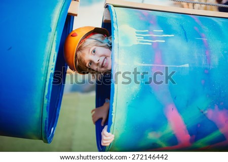 happy kid having fun and playing in plastic tubes, as adventure activity - stock photo