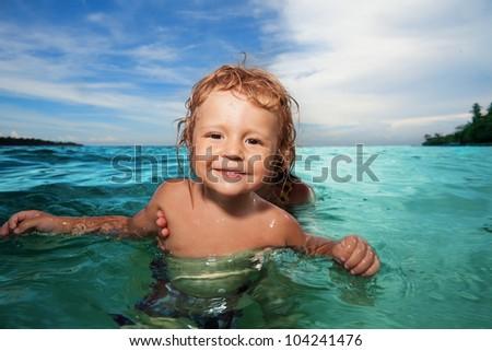 Happy kid having fun in the ocean - stock photo