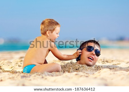 happy kid helping father in sand talk on the mobile phone - stock photo