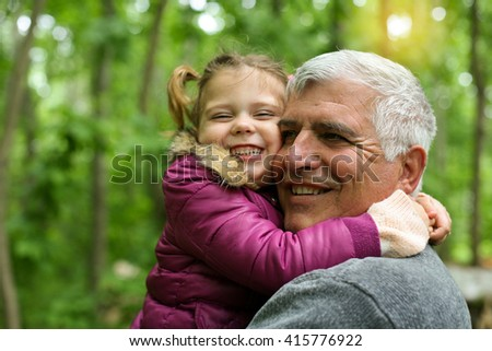 Happy kid hugging grandfather in the park.  - stock photo