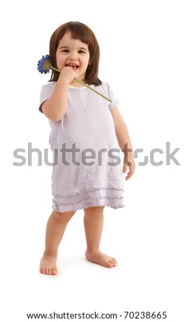 Happy kid in cute dress posing with spring flower, laughing at camera.?