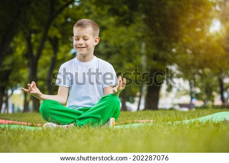 happy kid is doing exercises in the summer park - stock photo
