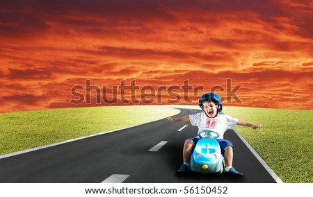 Happy kid on green meadow driving a car - stock photo