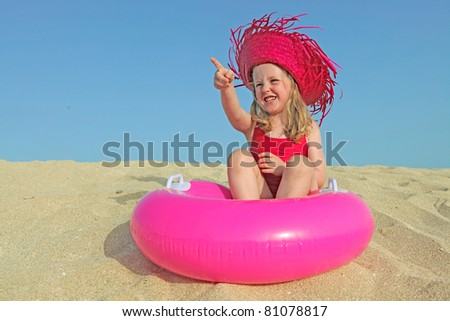happy kid on vacations on beach pointing at bland copy space - stock photo