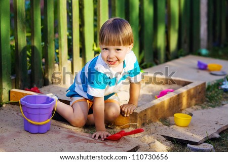 Happy kid playing in a sandbox - stock photo