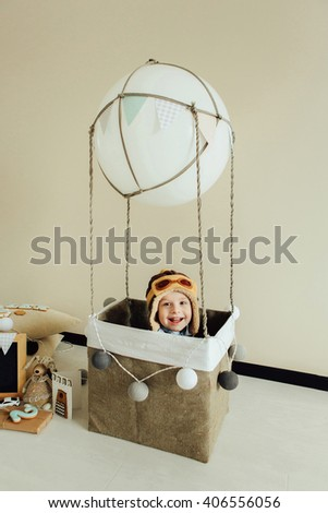 Happy kid playing in handmade basket of air balloon. Child having fun at home. Young pilot indoors at solid color background with copy space. Boy in hat looking at camera. Blank chalkboard. - stock photo