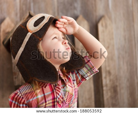 Happy kid playing in pilot helmet near the wooden background - stock photo