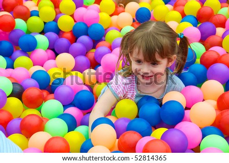 Happy kid playing in the colorful balls