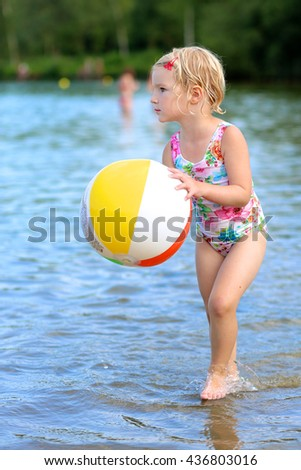 Happy kid playing in the lake with inflatable ball. Healthy smiling toddler girl enjoying summer vacation outdoors.  - stock photo