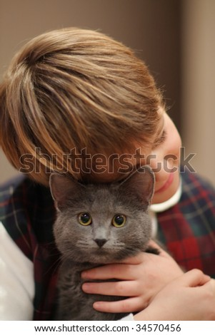 Happy kid playing with beautiful cat - stock photo