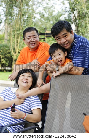 happy kid playing with his uncle and aunt - stock photo