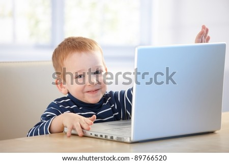 Happy kid playing with laptop, sitting at table, smiling.? - stock photo