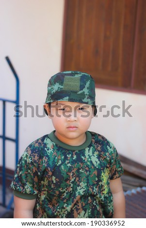 Happy kid playing with military camouflage uniforms - stock photo
