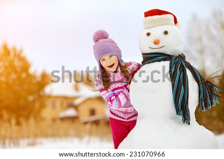 happy kid playing with snowman. funny little girl on a walk in the winter outdoors - stock photo