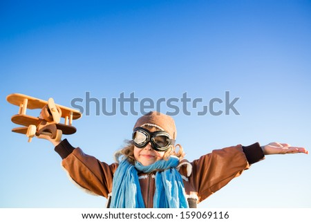 Happy kid playing with toy airplane against blue sky background. Copy space for your text