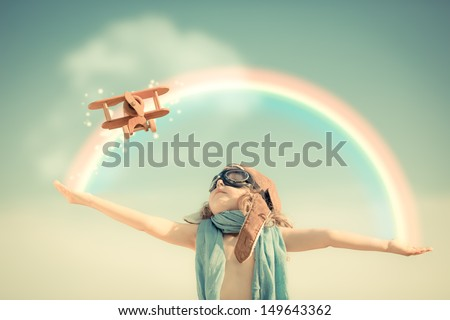 Happy kid playing with toy airplane against summer sky background - stock photo