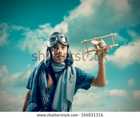 Happy kid playing with toy airplane in the sky - stock photo