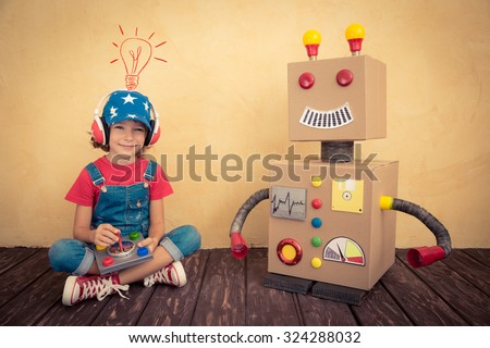 Happy kid playing with toy robot at home. Retro toned - stock photo