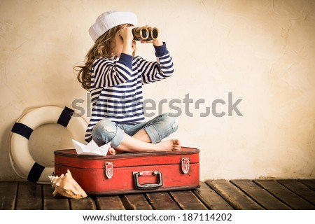 Happy kid playing with toy sailing boat indoors. Travel and adventure concept. Child, summer, vacation - stock photo