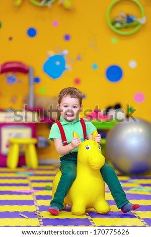happy kid riding a toy in kindergarten - stock photo
