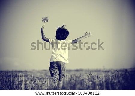 Happy kid running on beautiful field - stock photo