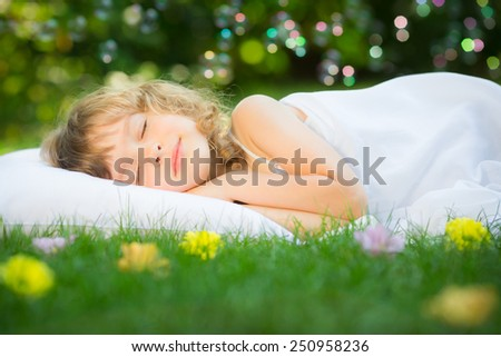 Happy kid sleeping on green grass outdoors in spring garden - stock photo