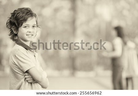Happy kid smiling in schoolyard with other chilldren playing on background. - stock photo