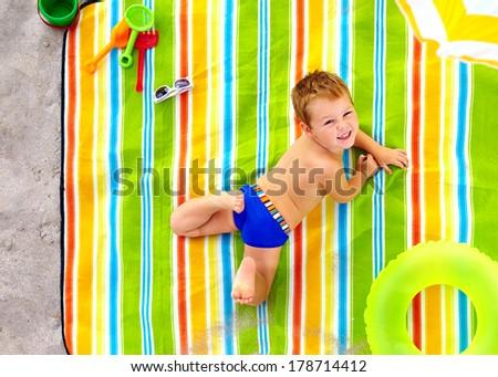 happy kid sunbathing on colorful beach - stock photo