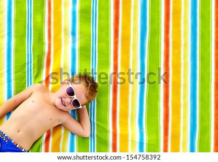 happy kid sunbathing on colorful blanket - stock photo