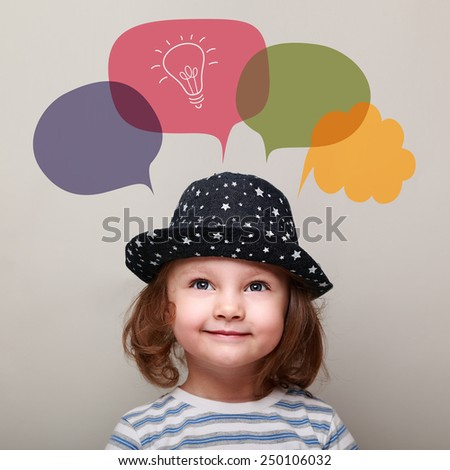 Happy kid thinking and looking up on idea bulb in bubble on grey background. Closeup portrait - stock photo