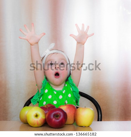 Happy Kid with apples sitting at the table. - stock photo
