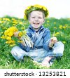 Happy kid with diadem and dandelions on green grass - stock photo